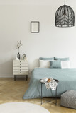 Breakfast on a metal table in front of a bed with sage green bedding in a natural bedroom interior. A beige drawer cabinet by the bed. Black lamp hanging from a ceiling. Real photo - 221389199