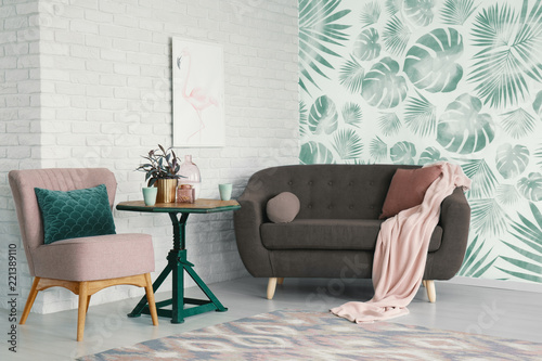 Sticker Table with flowers between pink chair and settee in apartment interior with poster and wallpaper. Real photo