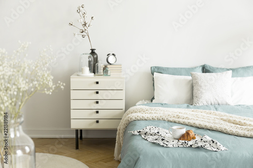 A bright bedroom interior with sage green and white bedding, pillows on bed and a drawer nightstand. Real photo. - 221389184