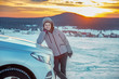 canvas print picture - Woman at the car in snow landscape with sunset