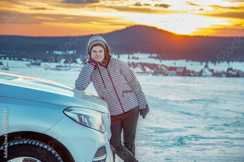 Woman at the car in snow landscape with sunset