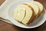 Slices of vanilla roll cake in white plate on wooden table. - 221391362