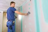 apartment interior construction - worker plastering gypsum board wall - 221394757