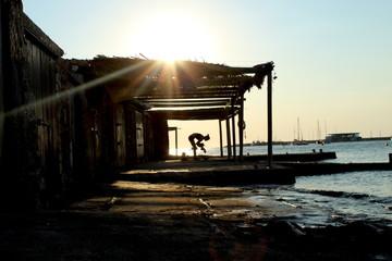 Sunset silhouette: woman dancing in fish shack. San Antonio de Portmany, Ibiza. © laura