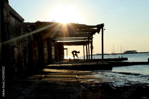 Sunset silhouette: woman dancing in fish shack. San Antonio de Portmany, Ibiza.