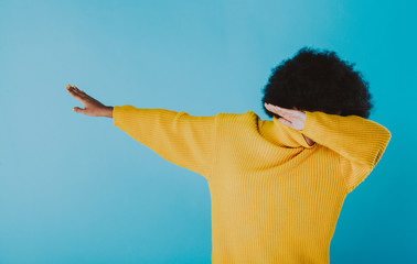 Woman dabbing on colored backgrounds. young adult with afro haircut making the dab move
