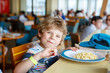 Leinwanddruck Bild - Cute healthy preschool kid boy eats pasta noodles sitting in school or nursery cafe. Happy child eating healthy organic and vegan food in restaurant. Childhood, health concept.