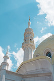 The tall, white tower of the mosque against the blue sky. - 221415588