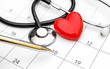 Pen pointing on calendar with stethoscope and red heart. Date for medical examiner.
