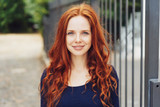 Pretty young woman with gorgeous curly red hair - 221420517
