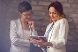 Two businesswoman looking photos on pad