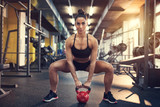Female doing squats using kettle bell weight