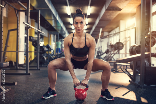Leinwandbild Motiv Female doing squats using kettle bell weight