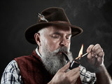 dramatic portrait of gray bearded senior man in hat smoking tobacco pipe. view of Austrian, Tyrolean, Bavarian old man in national traditional costume in retro style. - 221427754