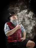 dramatic portrait of gray bearded senior man in hat smoking tobacco pipe. view of Austrian, Tyrolean, Bavarian old man in national traditional costume in retro style. - 221427965