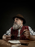 The senior bearded man sitting at table and clogging the tobacco in pipe. The male hands close up. Bavaria. a man dressed in traditional Bavarian or Austrian national traditional costume - 221429514