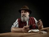 The senior bearded man sitting at table and clogging the tobacco in pipe. The male hands close up. Bavaria. a man dressed in traditional Bavarian or Austrian national traditional costume - 221429571