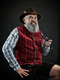 dramatic portrait of gray bearded senior man in hat smoking tobacco pipe. view of Austrian, Tyrolean, Bavarian old man in national traditional costume in retro style. - 221430972