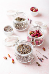 Dried rose flower buds and flowers in glass jars. Herbal tea, cleansing, organic bio products