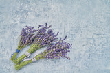 Three bouquet of lavender flowers on blue background. Copy space, top view. - 221431592