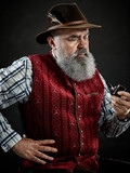 dramatic portrait of gray bearded senior man in hat smoking tobacco pipe. view of Austrian, Tyrolean, Bavarian old man in national traditional costume in retro style. - 221431711