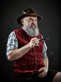 dramatic portrait of gray bearded senior man in hat smoking tobacco pipe. view of Austrian, Tyrolean, Bavarian old man in national traditional costume in retro style. - 221431995