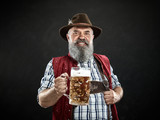 Germany, Bavaria, Upper Bavaria. The smiling man with beer dressed in in traditional Austrian or Bavarian costume in hat holding mug of beer at studio - 221432102