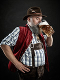 Germany, Bavaria, Upper Bavaria. The smiling man with beer dressed in in traditional Austrian or Bavarian costume in hat holding mug of beer at studio - 221432373