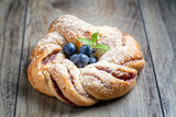 Blueberry pleated bun with powdered sugar and fresh berries. - 221432388