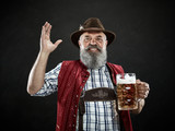 Germany, Bavaria, Upper Bavaria. The smiling man with beer dressed in in traditional Austrian or Bavarian costume in hat holding mug of beer at studio - 221432571