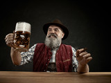 Germany, Bavaria, Upper Bavaria. The smiling man with beer dressed in in traditional Austrian or Bavarian costume in hat holding mug of beer at studio - 221432709