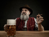 Germany, Bavaria, Upper Bavaria. The smiling man with beer dressed in in traditional Austrian or Bavarian costume in hat holding mug of beer at studio - 221432785