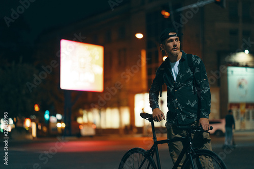 Cyclists standing on the road aside his classic bike while watch