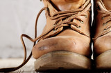 Yellow leather used work boots on concrete background closeup. Place for text - 221436541