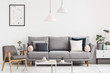 Leinwanddruck Bild - Grey armchair next to settee in white apartment interior with poster and lamps above table. Real photo