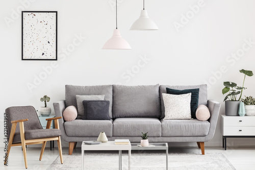 Leinwanddruck Bild Grey armchair next to settee in white apartment interior with poster and lamps above table. Real photo