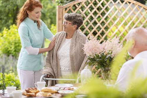 Leinwanddruck Bild A tender caretaker assisting an elderly woman with a walker during an afternoon snack time on a patio in the garden of a private nursing home.