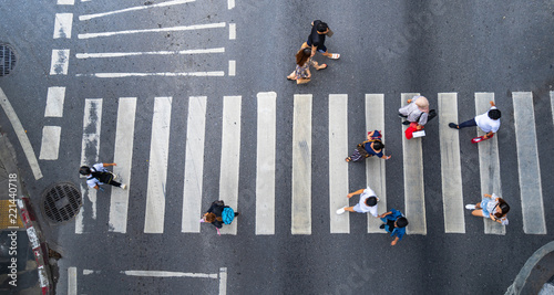 Leinwanddruck Bild Aerial photo top view of people walk on street in the city over pedestrian crossing traffic road