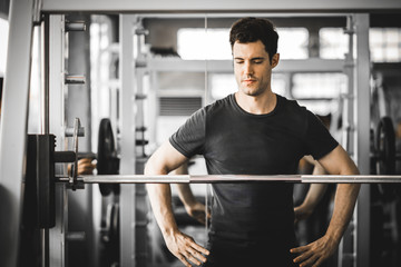 Fit caucasian handsome young man and big muscle in sportswear. Young man standing and looking machine weight lifting in a gym. Healthy sports lifestyle, Fitness concept. with copy space © Phawat Topaisan