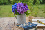 Old opened book, glasses, cup of coffee and bouquet of blue hydrangea on vintage table in the garden - 221444733
