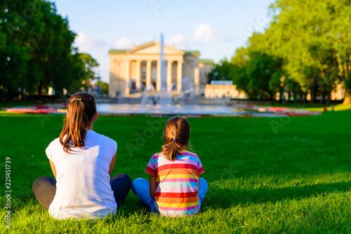 dzieci siedzące na trawie w parku przed Teatrem Wielkim - neoklasyczna opera w Poznaniu, Polska - w promieniach zachodzącego słońca