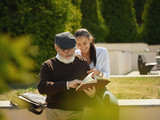 Help someone you love. Portrait of young smiling girl embracing grandfather with book against city park. community and family lifestyle concept - 221453565