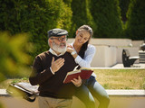 Help someone you love. Portrait of young smiling girl embracing grandfather with book against city park. community and family lifestyle concept - 221453706