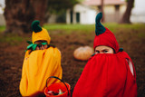 Twin sisters tricking outdoors on halloween - 221453964