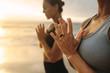 Leinwanddruck Bild - Women practicing yoga at the beach