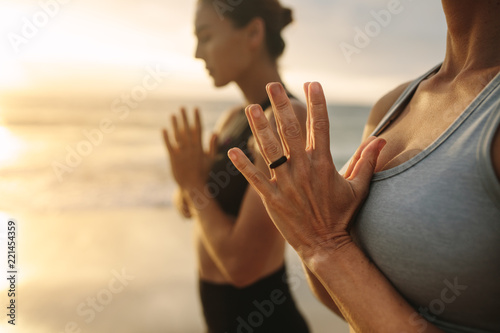 Leinwanddruck Bild Women practicing yoga at the beach