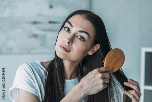 Leinwanddruck Bild young brunette woman combing hair with hairbrush and looking at camera