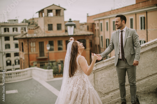 Bride and groom walking outdoors at Spagna Square and Trinita' dei Monti in Rome, Italy - 221456178