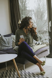 Curly hair young woman using mobile phone and holding mug while sitting on sofa - 221456370