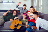 Cheerful group of friends with a guitar at a party in a room. - 221457131